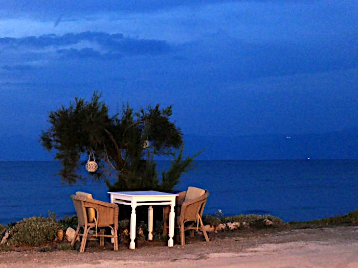 Foto van tafel stoelen bij boom op boulevard