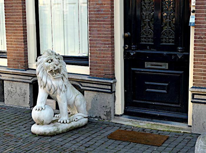 Foto van beeld van leeuw op stoep voor huis