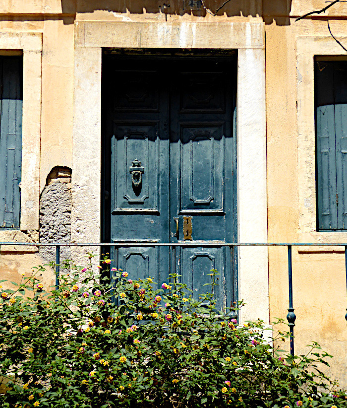 Foto van houten dubbele deur met metalen klopper