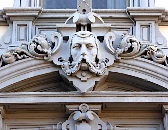 Foto van gevel met beeld van hoofd met grote snor