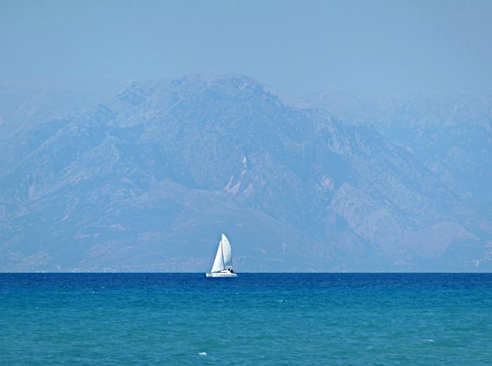 Foto van zeilboot voor bergachtige kust