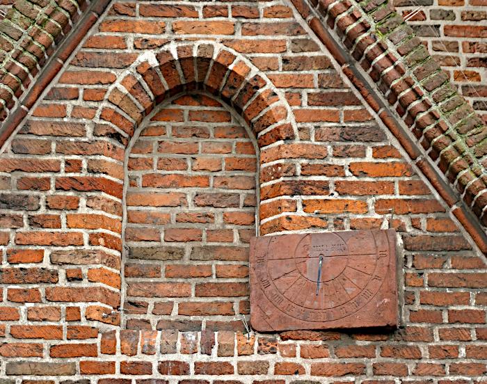 Foto van zonnewijzer aan muur van kerk