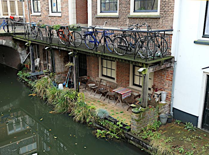 Foto van terras aan water met daarboven fietsen op straatniveau
