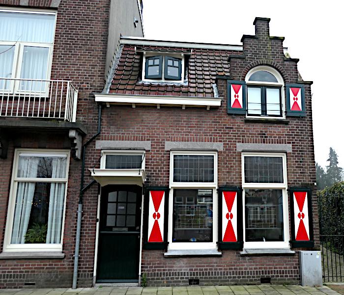 Foto van klein huis met roodwitte luiken