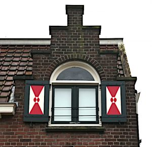Foto van huisje met roodwitte luiken (detail)
