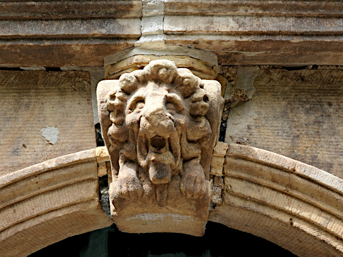 Foto van leeuwenkop boven stenen poort