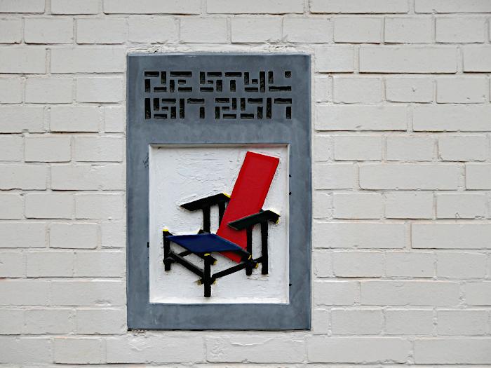 Foto van stenen plaquette met stoel van Rietveld