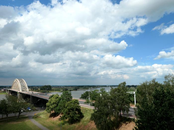 Foto van rivier met brug en wollkenlucht