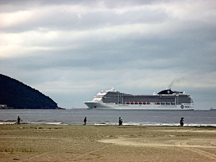 Foto van cruiseschip dat langs strand vaart