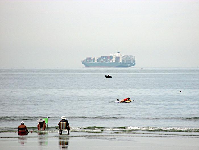 Foto van strandgangers met zicht op containerschip