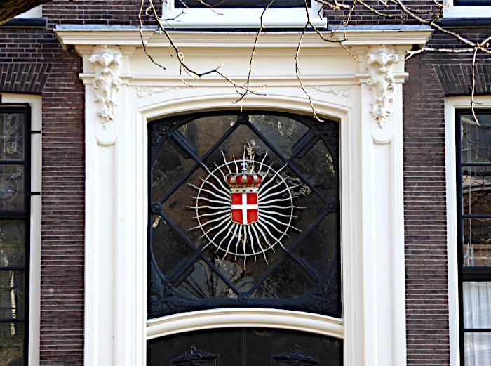 Foto van raam boven deur met decoratie (wapen)