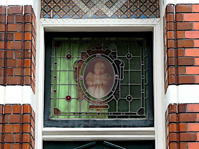 Foto van bovenlicht met afbeelding van meisje in glas in lood