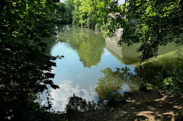 Foto van bomen en fort en lucht reflecterend in water