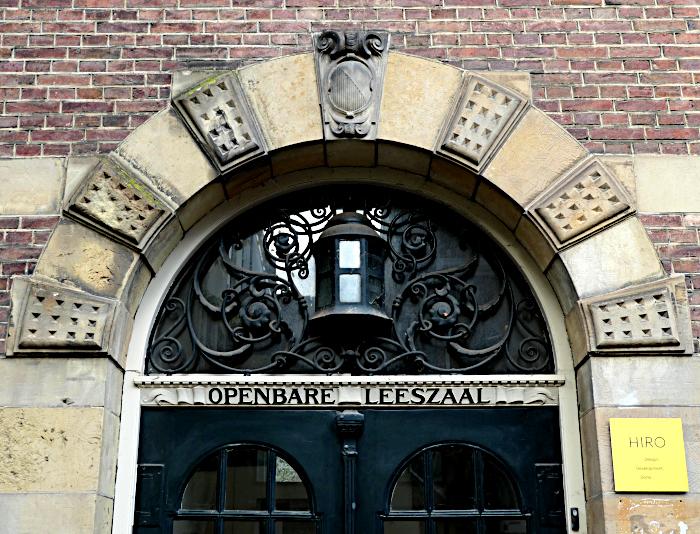 Foto van boog boven deur en opschrift 'Openbare Leeszaal'