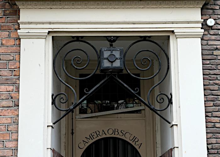 Foto van smeedijzeren versiering met camera boven entree