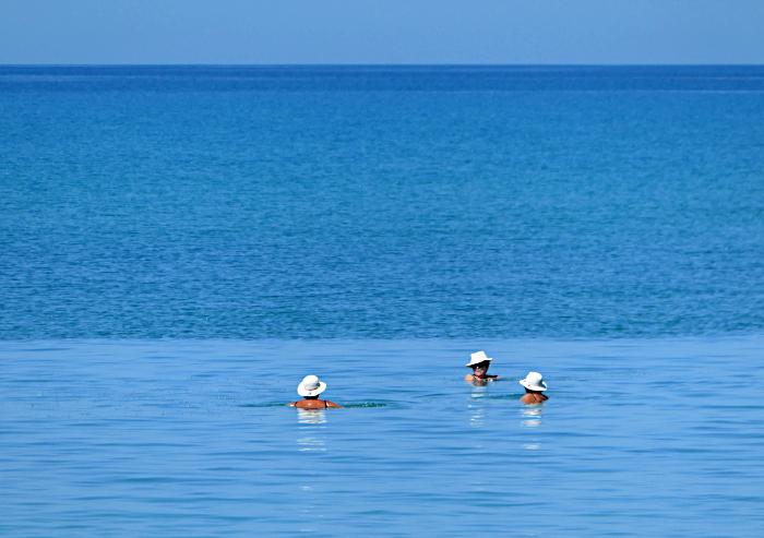 Foto van hoofden met hoedjes in blauwe zee